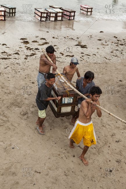 PHILIPPINES, Palawan, Sabang,  - February 8, 2011: boats drop supplies on the main beach in the town of Sabang, men carry the supply boxes to their trucks to make deliveries