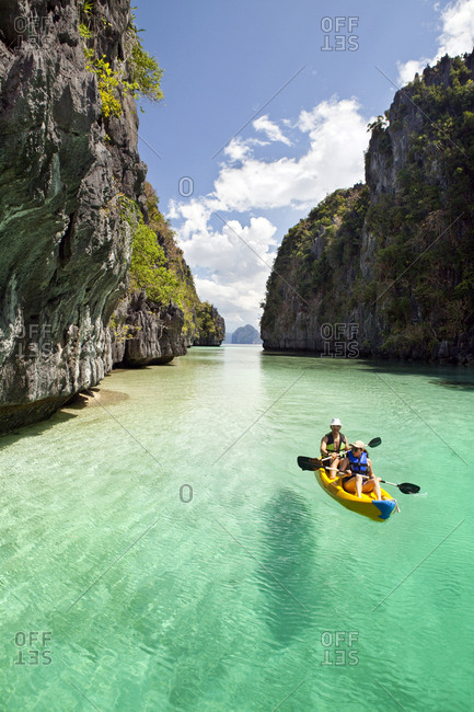PHILIPPINES, Palawan, El Nido, - February 10, 2011:  Miniloc Island, tourists kayak through the crystal clear waters of Big Lagoon on Miniloc Island located in Bacuit Bay in the South China Sea