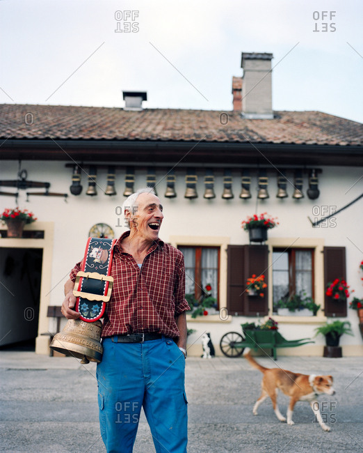 SWITZERLAND, Motiers,  - March 20, 2017: George Montandon stands in front of his home holding a cow bell that was given to him by a friend for his 45th wedding anniversary, Jura Region