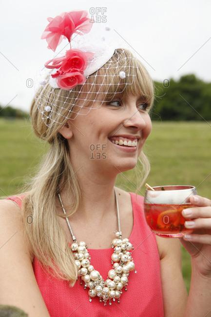 USA, Tennessee, Nashville,  - May 12, 2012: Iroquois Steeplechase, woman drinking Moonshine Cherry-Basil Blush