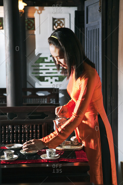 VIETNAM, Hue,  - April 15, 2010: Ms. Boi Tran's Hoang Vien restaurant, a woman in traditional dress pours tea