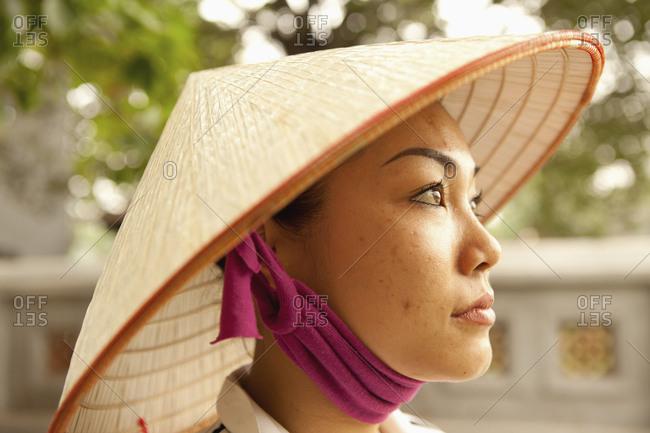 VIETNAM, Hanoi,  - April 12, 2010: portrait of a young woman wearing a non la or leaf hat, Hoan Kiem Lake