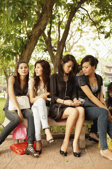 VIETNAM, Hanoi,  - April 12, 2010: young women sitting together on a bench by Hoan Kiem Lake