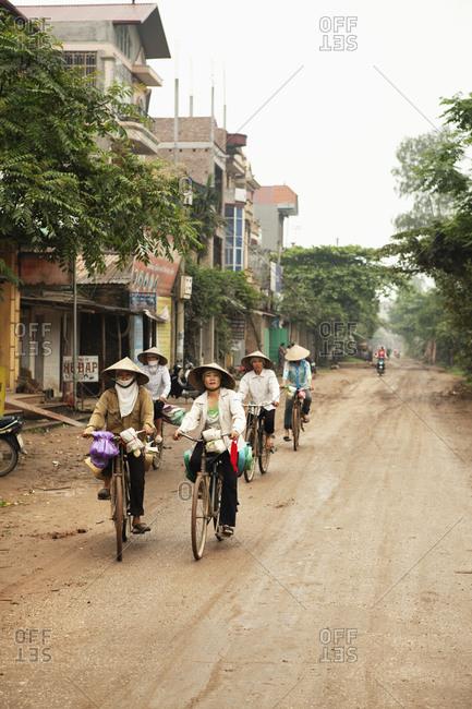 VIETNAM, Hanoi,  - April 13, 2010: Countryside, women ride their bikes along a rural road in Thanh Bac Ninh
