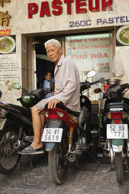 VIETNAM, Saigon, - April 18, 2010:  restaurant Pho Hoa aka Pho Hoa Pasteur, the owner sits on a moped out front of his establishment, Ho Chi Minh City