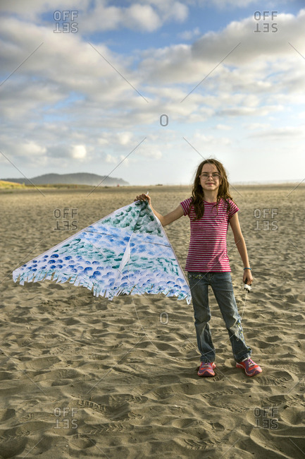 USA, Washington State, Long Beach Peninsula,  - August 20, 2014: International Kite Festival, portrait of Lorel Kirby holding her kite at the beach at the end of the day
