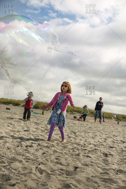 USA, Washington State, Long Beach Peninsula,  - August 21, 2014: Thorson kids chase and play with bubbles on the beach at the International Kite Festival