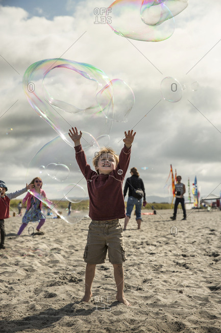 USA, Washington State, Long Beach Peninsula,  - August 21, 2014: kids chase and play with bubbles on the beach at the International Kite Festival