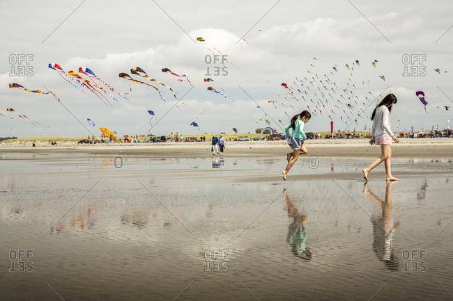 USA, Washington State, Long Beach Peninsula,  - August 21, 2014: International Kite Festival, sisters enjoy the beach at the kite festival