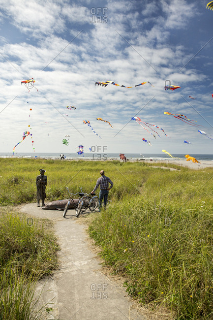 USA, Washington State, Long Beach Peninsula,  - August 21, 2014: International Kite Festival, watching kites by the Captain Lewis Clark and Sturgeon sculpture on the Discovery Trail