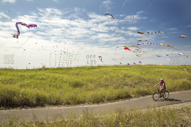 USA, Washington State, Long Beach Peninsula,  - August 21, 2014: International Kite Festival, woman riding her bike on the path that runs parallel to the Long Beach Boardwalk