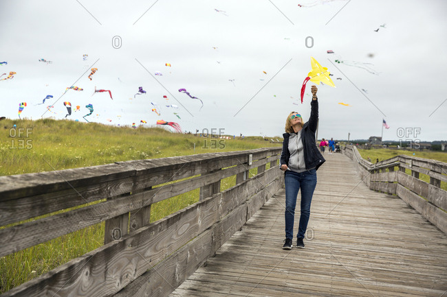 USA, Washington State, Long Beach Peninsula,  - August 22, 2014: International Kite Festival, a French woman flies a kite along the popular Long Beach Boardwalk
