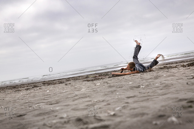 USA, Washington State, Long Beach Peninsula,  - August 22, 2014: International Kite Festival, Cameron Hendricks a young athletic boy flies a power kite that drags ends up dragging him along the sand