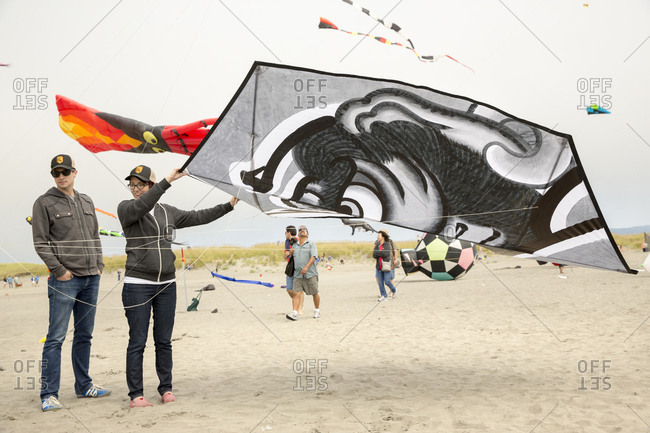 USA, Washington State, Long Beach Peninsula, - August 23, 2014: International Kite Festival, couple launch a large black and white Japanese style kite