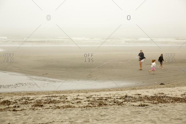 USA, Washington State, Long Beach Peninsula, - August 23, 2014: International Kite Festival, mother and children fly a kite