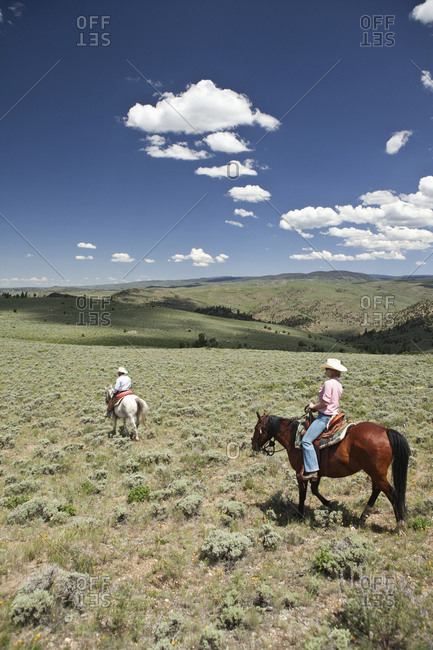USA, Wyoming, - June 30, 2010:  Encampment, a cowboy and cowgirl ride through an endless landscape, Abara Ranch