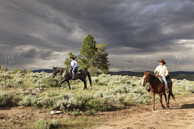 USA, Wyoming, - July 2, 2010:  Encampment, a man and woman ride horses under a dramatic sky, Abara Ranch