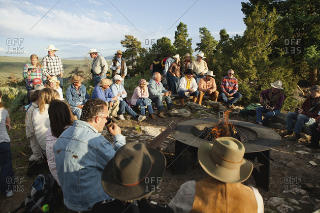 USA, Wyoming, - July 2, 2010:  Encampment, guests at a dude ranch sit around a campfire and listen to a man play the guitar and sing country western songs, Abara Ranch