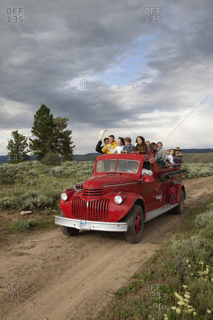 USA, Wyoming, - July 2, 2010:  Encampment, kids ride an old restored firetruck to a dinner cookout, Abara Ranch