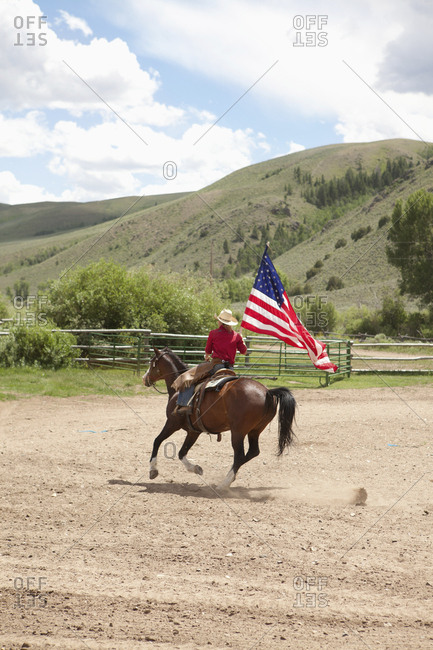 USA, Wyoming, - July 3, 2010:  Encampment, a young man rides his horse carrying the American flag, Abara Ranch