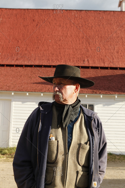 USA, Wyoming, - June 23, 2011:  Encampment,  cowboy with a large moustach satnds in front of a barn, Big Creek Ranch