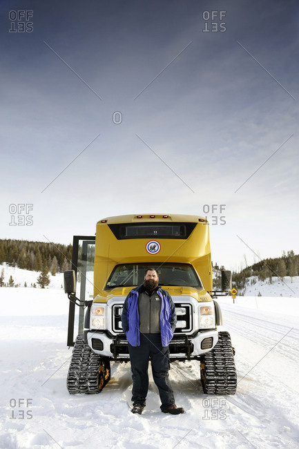 USA, Wyoming, Yellowstone National Park,  - January 1, 2000: portrait of a Yellowstone guide standing in front of a Snow coach on the road between Mammoth Hot Springs and Norris