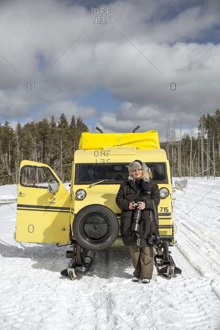 USA, Wyoming, Yellowstone National Park,  - January 1, 2000: a tourist stands in front of a Yellowstone Snow coach on the road in the Lower Geyser Basin