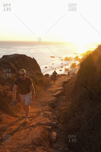 USA, California, Malibu,  - October 8, 2010: people walk up a trail from El Matador beach at sunset