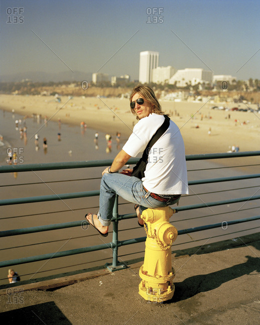 USA, California, Santa Monica, Los Angeles, - March 19, 2017:  a young man sits on a fire hydrant on the Santa Monica Pier with Santa Monica State Beach in the distance