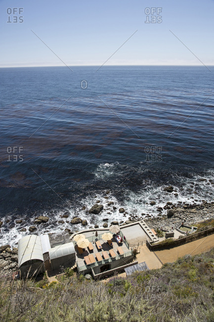 USA, California, Big Sur, Esalen,  - May 13, 2013: the hot spring baths and bath house at the Esalen Institute rest above the Pacific Ocean