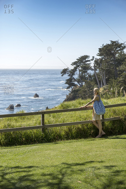 USA, California, Big Sur, Esalen,  - May 13, 2013: a woman strolls on the lawn by the Lodge in front of the Pacific Ocean, the Esalen Institute