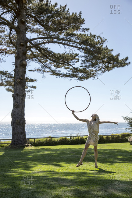 USA, California, Big Sur, Esalen,  - May 13, 2013: hula hooping on the lawn by the Lodge in front of the Pacific Ocean, the Esalen Institute
