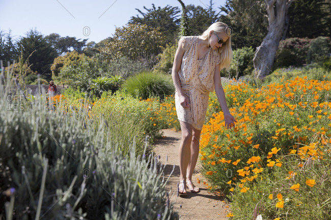 USA, California, Big Sur, Esalen,  - May 13, 2013: a woman walks in and enjoys the flowers in the Buddha Garden