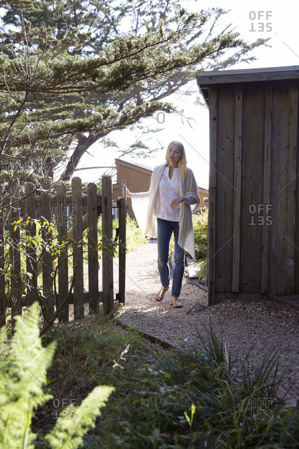 USA, California, Big Sur, Esalen,  - May 13, 2013: woman walks through a gate next to the Little Wooden Yurt at the Esalen Institute