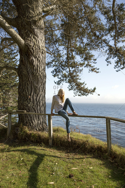 USA, California, Big Sur, Esalen,  - May 13, 2013: woman hops off of the fence near the Farm House with views of the Pacific in the distance, the Esalen Institute