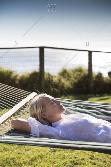 USA, California, Big Sur, Esalen,  - May 13, 2013: woman takes a rest on a hammock by the Farm House in the afternoon, the Esalen Institute