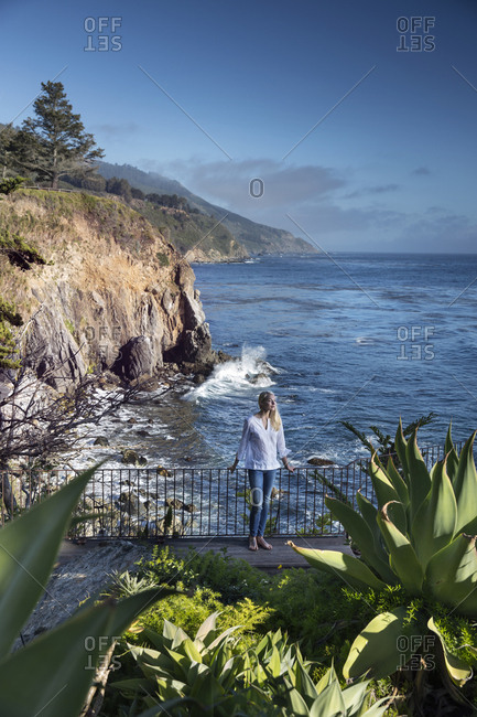 USA, California, Big Sur, Esalen,  - May 13, 2013: woman standing on the deck below the Murphy House with distant views of the Big Sur Coastline and the Pacific Ocean, the Esalen Institute