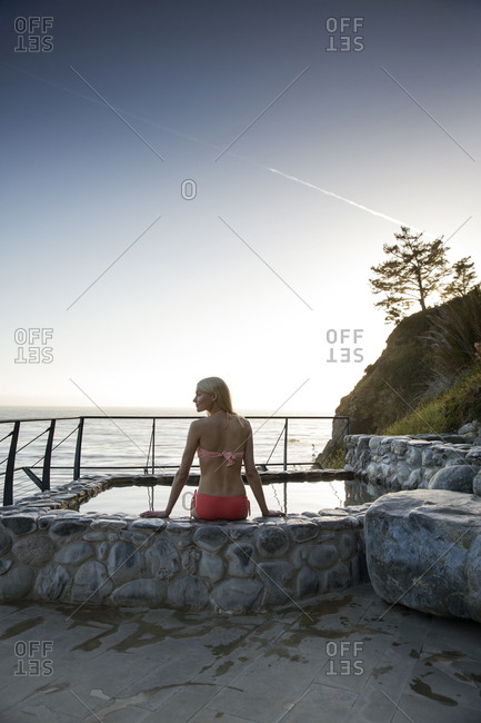 USA, California, Big Sur, Esalen,  - May 13, 2013: a woman sits on the edge of the hot spring at the Baths and takes in the evening view, the Esalen Institute
