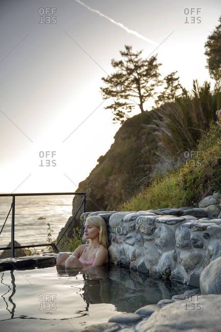 USA, California, Big Sur, Esalen,  - May 13, 2013: a woman sits in the Baths and takes in the evening view, the Esalen Institute