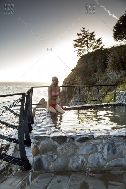 USA, California, Big Sur, Esalen,  - May 13, 2013: a woman sits in the Baths and looks out on the Big Sur coastline at sunset, the Esalen Institute
