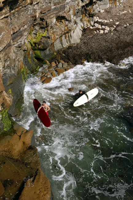 USA, California, San Diego,  - May 12, 2011: two surfers prepare to enter the water along Sunset Cliffs at Ocean Beach