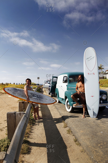USA, California, San Diego,  - May 12, 2011: Aaron Scott rests holding his surfboard on the hood of his car
