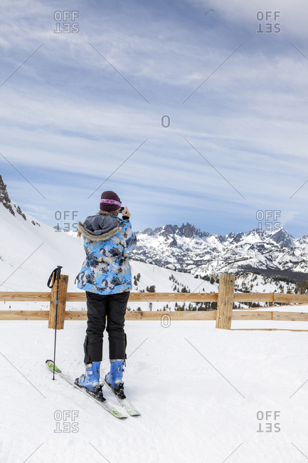 USA, California, Mammoth,  - March 5, 2011: a female skier takes a break to snap a photo of the captivating scenery at Mammoth Ski Resort