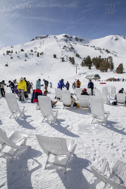 USA, California, Mammoth,  - March 5, 2011: several skiers and snowboarders rest at the bottom of the chairlift at Mammoth Ski Resort