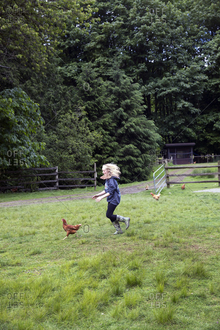 CANADA, Vancouver, British Columbia,  - May 25, 2013: young girls chase chickens in Port Graves, Gambier Island, Howe Sound