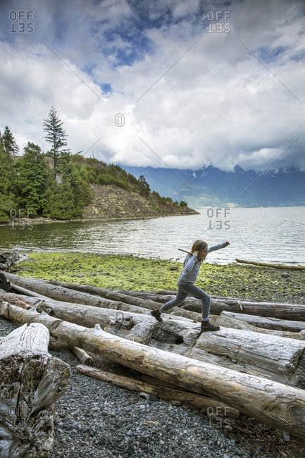 CANADA, Vancouver, British Columbia,  - May 25, 2013: young girl walks on driftwood logs at Brigade Bay on Gambier Island, in the Howe Sound with the Britannia Range in the distance