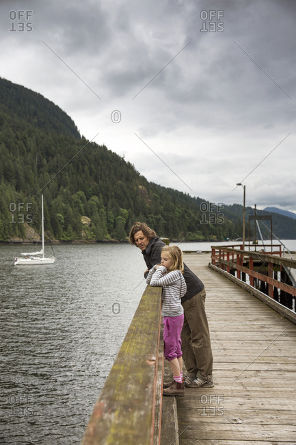 CANADA, Vancouver, British Columbia,  - May 26, 2013: father and daughter lean on a railing on a dock on Gambier Island, in the Howe Sound