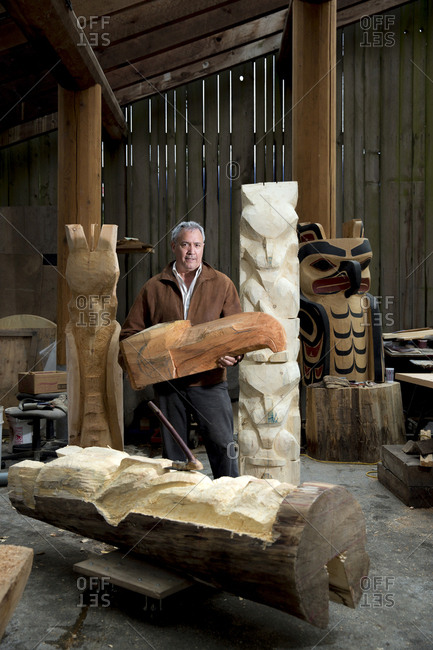 CANADA, Vancouver, British Columbia,  - May 27, 2013: Haida Carver holds the head of a raven and stands next to totems at his shop on Granville Island