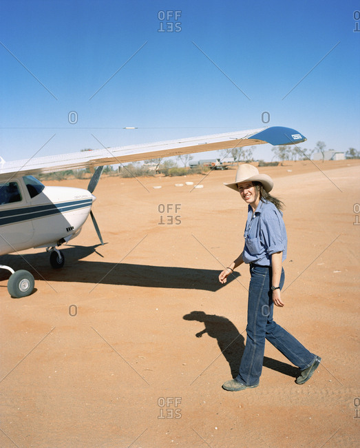 AUSTRALIA, Outback, - January 22, 2010:  portrait of a young female pilot walking towards plane. She is one of the youngest bush pilot.