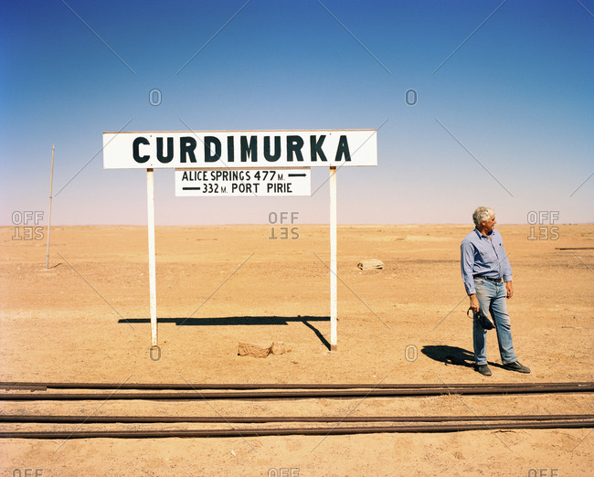 AUSTRALIA, Curdimurka,  - January 22, 2010: the Outback, Pilot Trevor Wright standing by signboard and railroad tracks in the outback